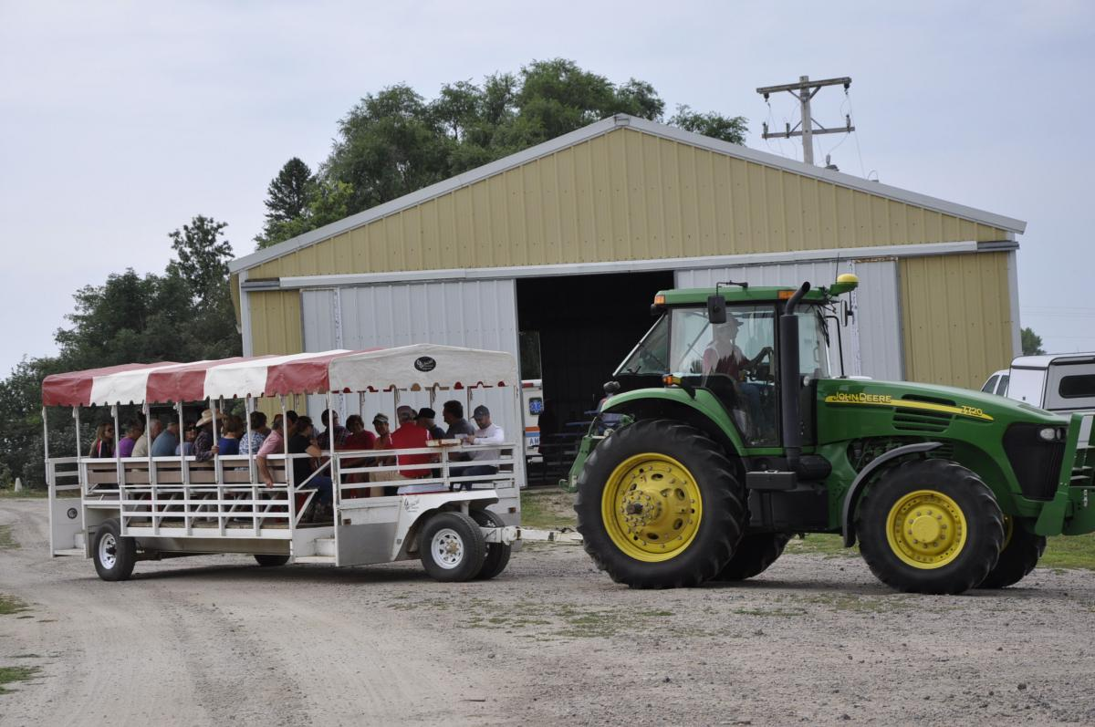 A trailer of visitors moves out to the field to view the latest crop and crop pest research.