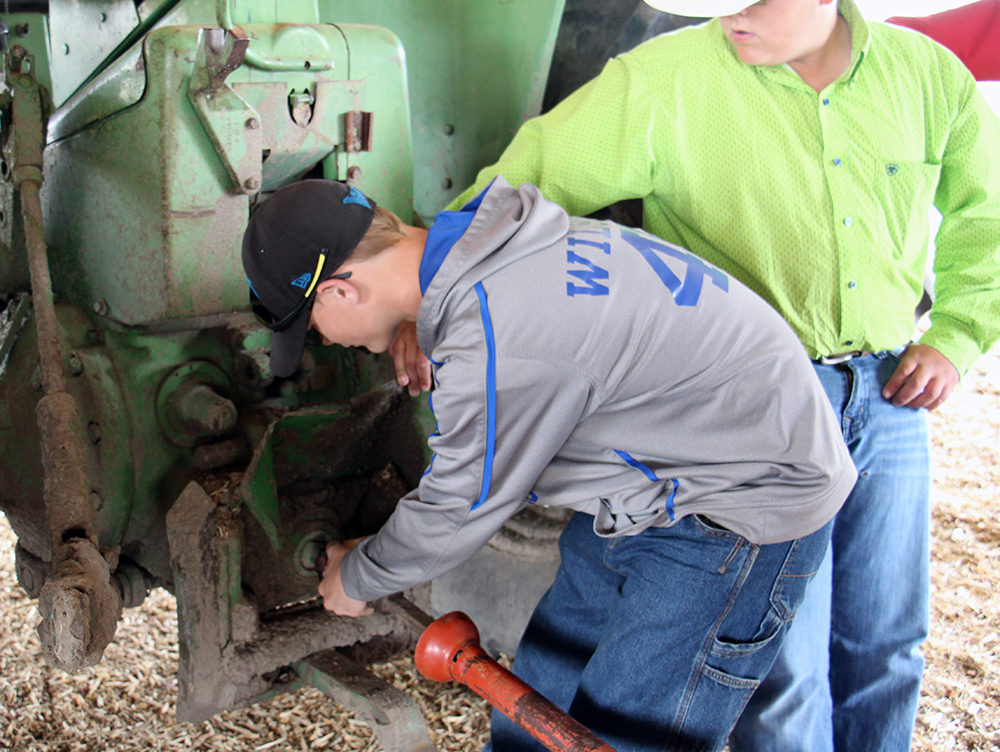 Two youth practicing proper connection procedures for a tractor PTO drive.