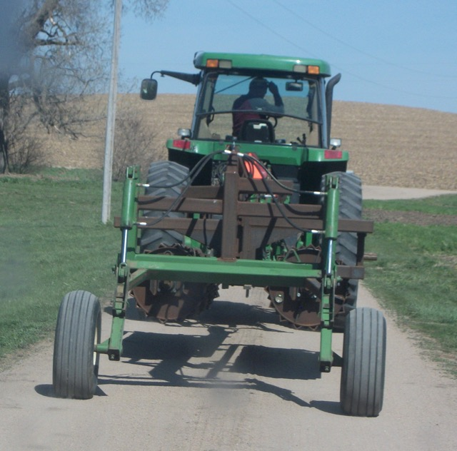 The rolling-crimper in transport down a country road.