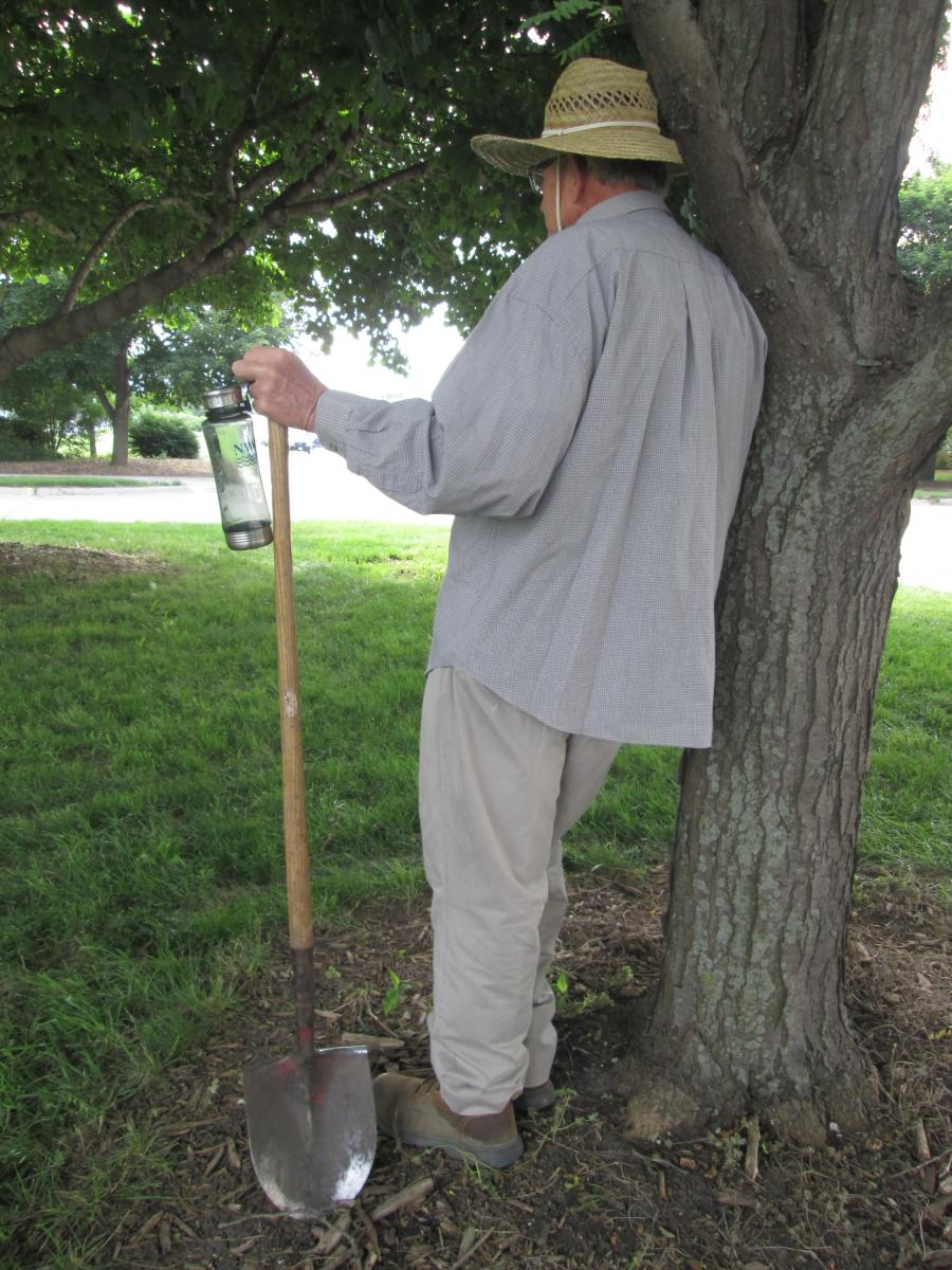 A man wearing light-colored clothing standing with a water bottle in the shade of a tree