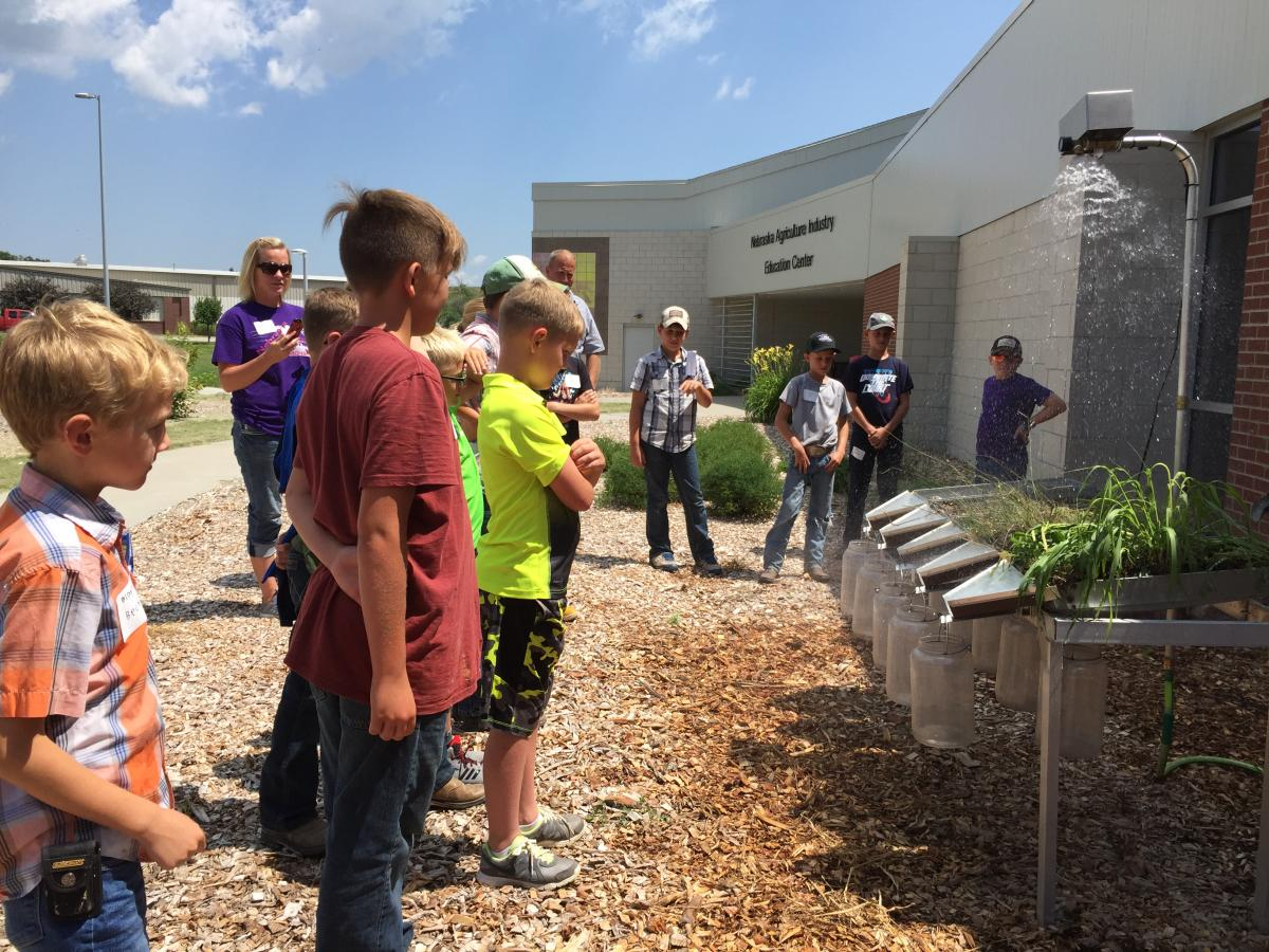 Youth viewing a rainfall simulator at the 2018 Youth Field Day