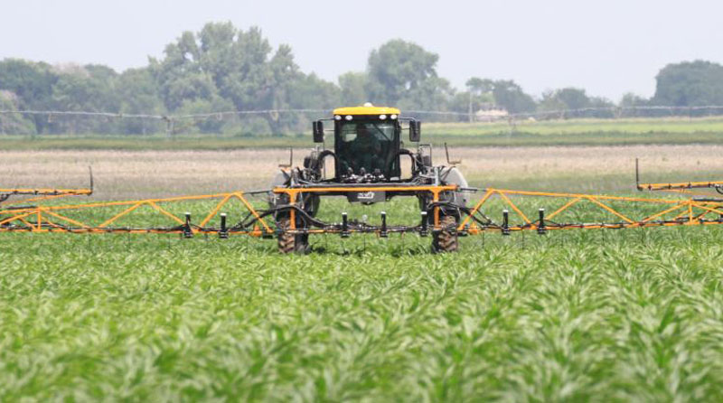 A tractor applies nitrogen to corn