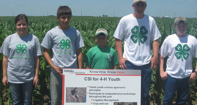 CSI youth holding sign in front of corn rows