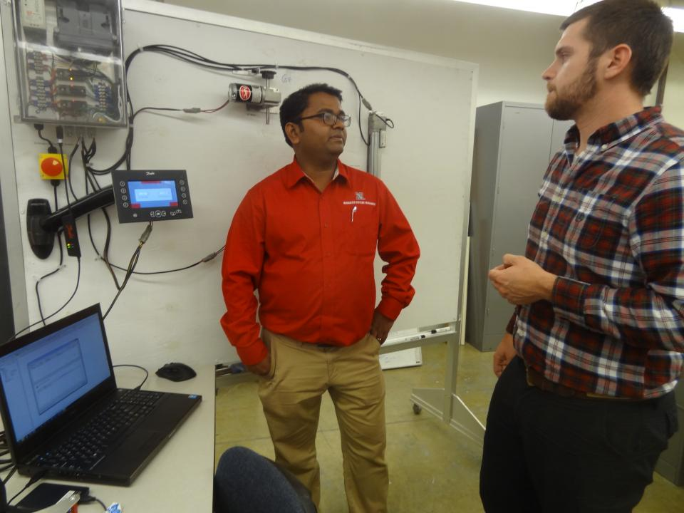 Biological Systems Engineering Assistant Professor Santosh Pitla (left) talks with BSE Graduate Student John Evans about the class they're teaching where students explore access and analysis of operational data from tractors.