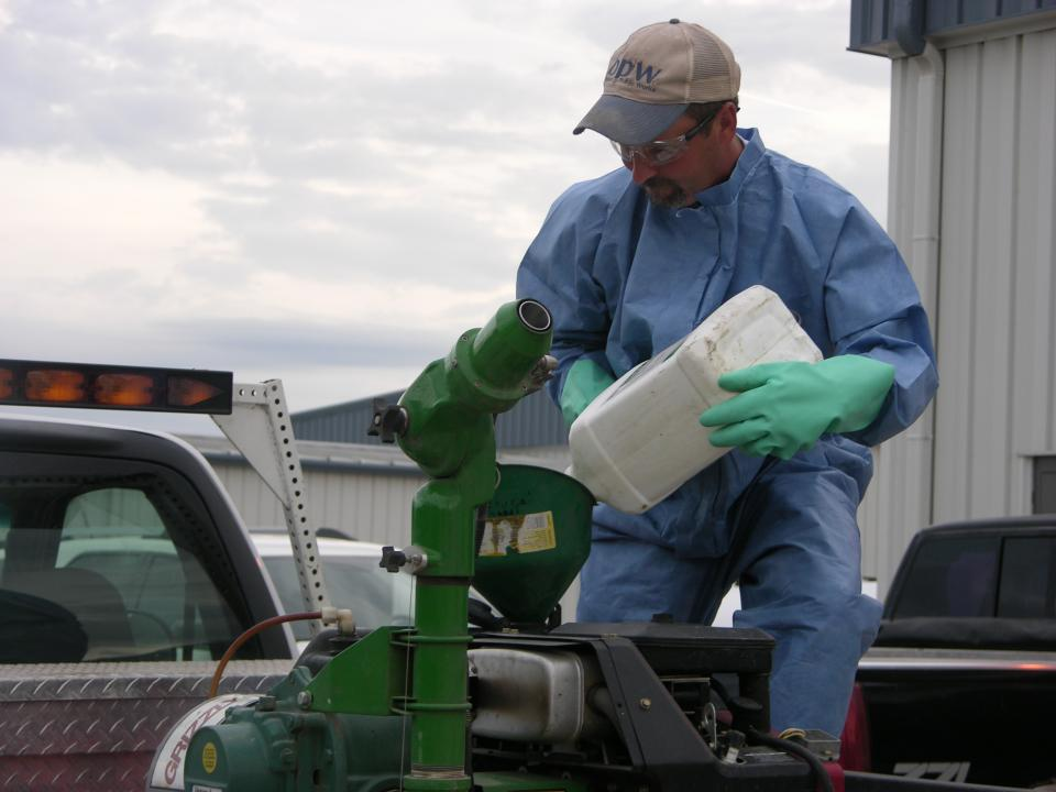 Photo of gloved pesticide applicator