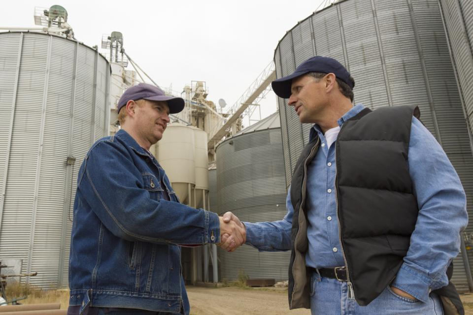 Two farmers standing in front of grain bins shaking hands