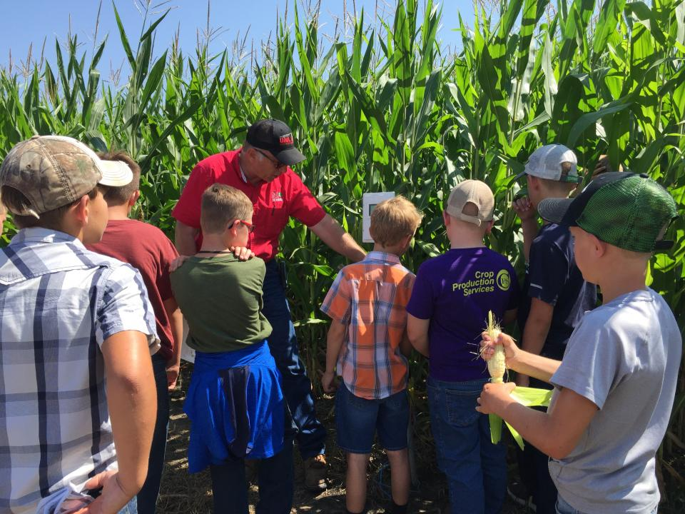 Figure 1. Extension Educator Chuck Burr demonstrating to youth how a crop moisture sensor works in a field of corn.