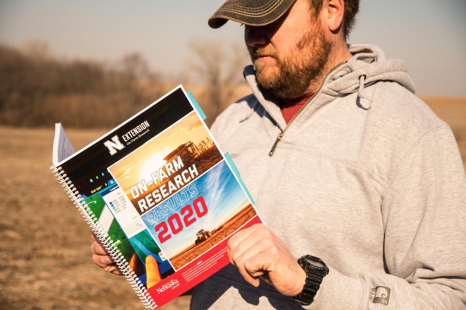 farmer reading On-Farm Research report