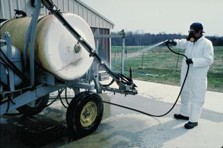 Dressed in personal protective gear and cleaning a sprayer