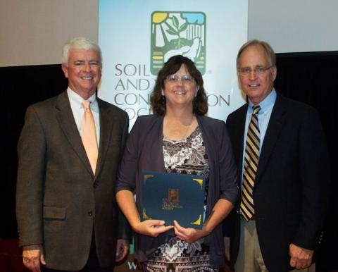 NRCS Resource Conservationist Claudia Stevenson receiving the International SWCS Commendation Award at the international meeting in July from (left) association executive director Jim Guilliford and association president Jon Scholl.
