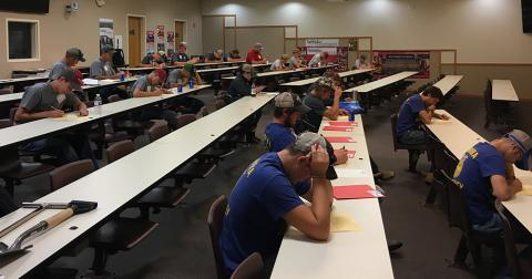 students taking a written test in a college classroom