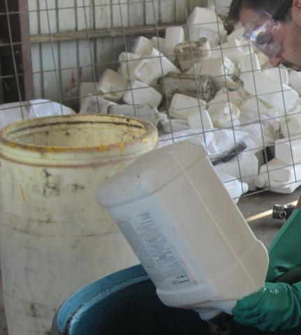 Lucas Burch wears gloves and safety glasses while triple rinsing a pesticide container.