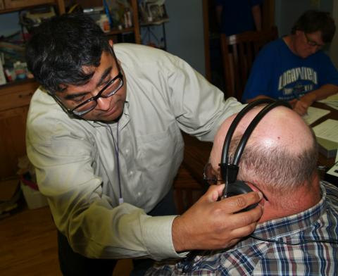 A researcher from the UNMC Center for Public Health works with a Nebraska farmer to fit protective ear wear.