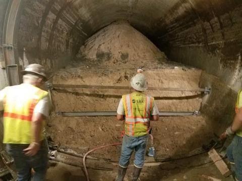 Workers examine the site of the smaller of the two tunnel collapses.