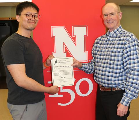 Xin Qiao (left), irrigation and water management specialist and principal investigator, and Jack Whittier, Panhandle Center Director of Research and Extension, accept the award from the Nebraska Environmental Trust fund to establish SDI research with livestock effluent.