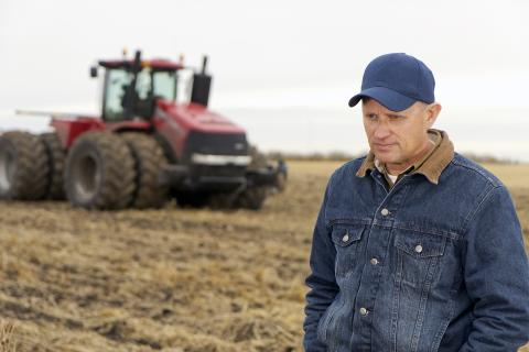 Photo of a farmer in a field in contemplation
