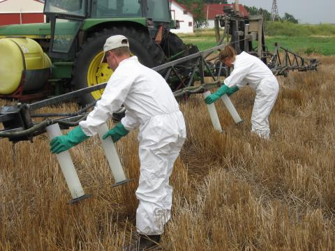 Two workers filling pesticide containers