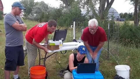 Aaron Mittelstet, Troy Gilmore, Mikaela Cherry and Didier Gatsmana sampling groundwater