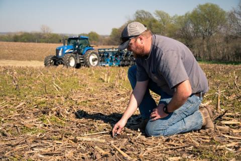 A farmer inspecting soil