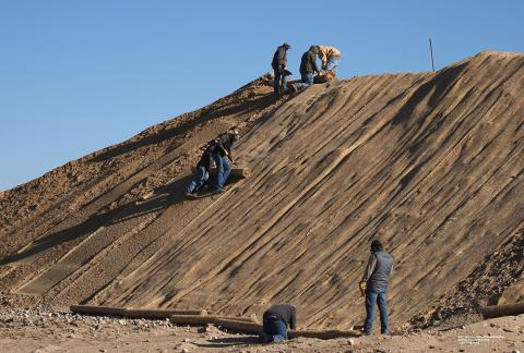 Irrigation District staff lay down a fabric mat to reduce erosion of excavated soil.