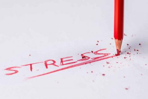 "Image of a red pencil breaking as it writes the word ""Stress"""